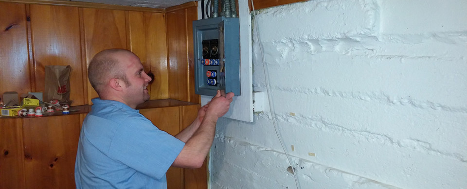 Electrician removing the cover from a fuse panel